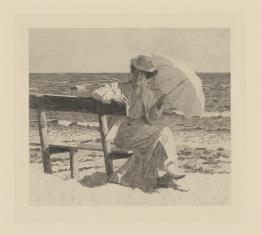 Kobieta siedząca na ławce nad brzegiem morza