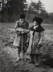 Dwaj chłopi w kożuszkach na tle lasu