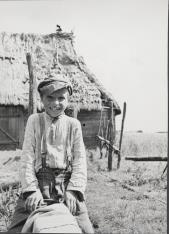 Mały Poleszuk siedzący okrakiem na żerdzi
