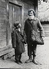Chłop i chłopiec przed chatą