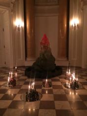 W pomieszczeniu galerii rzeźba przedstawiająca nagą kobietę na skale, kobieta prezentuje dłońmi waginę, tytułowe Źródło, dookoła na podłodze w kilku grupach płoną świece.