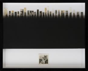 Zdjęcie pracy artysty składające się pociętych w pionowe paski czarnobiałych fotografii ułożonych w rząd w górnej części. Po środku czarny poziomy prostokąt, u dołu mała kwadratowa fotografia.