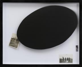 Zdjęcie pracy artysty w czarnej ramie: duży czarny owal w centralnej i prawej części, i dwie małe, stare, czarnobiałe fotografie.