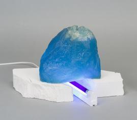 Zdjęcie rzeźby złożonej z trzech elementów: niebieskiej transparentnej formy przypominającej górę, jej białej podstawy z betonu i przechodzącej przez jej środek fioletowej świetlówki w białej oprawie zamocowanej w podstawie.