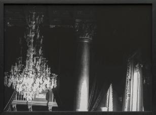 Fotografia czarnobiała pałacowego mocno zacieniowego wnętrza. Po lewej duży kryształowy żyrandol, w centrum kolumna, w głębi po prawej fragment zasłon.