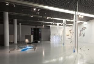 Widok wystawy w ms2. Duża, przestronna sala: białe ściany, metalowa kratownica na suficie, jasnoszara podłoga, po lewej rząd kolumn. W głębi czarne drzwi wejściowe. Na podłodze i po prawej stronie instalacje wieloelementowe.