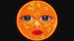 W centrum kadru na czarnym tle widoczna okrągła, żółtopomarańczowa tarcza słońca posiadająca duże niebieskie oczy, czerwone usta i nos.