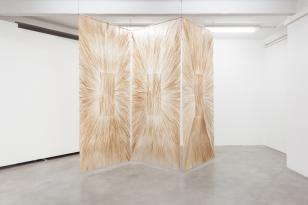 Zdjęcie przedstawiające pracę podwieszoną do sufitu, złożoną z trzech prostokątnych półprzezroczystych paneli, z prostokąta w centrum każdego promieniście rozchodzą się jasnobrązowe, płynne linie.