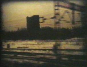 Kadr z filmu przedstawiający tory i przewody kolejowe oraz budynek na tle nieba o kolorze pomarańczowo-żółtym kolorze, całość lekko rozmyta.