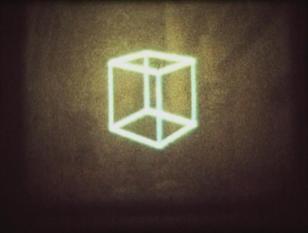 Ciemne zdjęcie szkieletu sześcianu. Nie widać, żeby obiekt był na czymkolwiek zawieszony, wygląda jakby unosił się w przestrzeni. Wykonany jest ze świecących elementów, dlatego środkowa część zdjęcia jest rozświetlona.