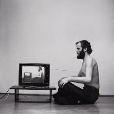 Czarnobiałe zdjęcie przedstawia rozebranego od pasa w górę mężczyznę siedzącego ze skrzyżowanymi nogami profilem do widza, zwrócony jest twarzą do telewizora na niskim stołeczku, na ekranie powtarza się ten właśnie obraz, sekwencja trwa w nieskończoność.