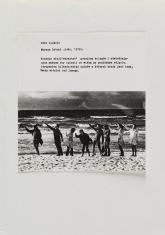 Na zdjęciu praca składająca się z poziomej kartki z opisem, i ułożonego pod nią czarnobiałego zdjęcia, przedstawiającego 8 osób na plaży na tle morza wznoszących prawe ręce do góry.