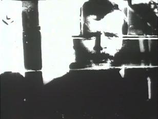 Czarno-biała klatka filmu przedstawiająca ramiona i twarz mężczyzny z wąsami i brodą, jego twarz otaczają pionowe i poziome białe linie.