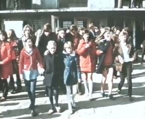 Na zdjęciu duża grupa dzieci i młodzieży idzie w stronę widza, w tle budynek. Dużo kurtek w które ubrani są ludzie jest w kolorze czerwonym.