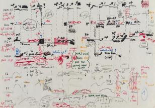 Kartka w poziomie, na niej zapis partytury utworu. Różniące się kolorem symbole literowe, graficzne i fragmenty tekstów tworzą wielowymiarową strukturę zapisu.