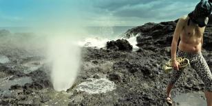 Kadr z filmu przedstawia skalisty brzeg oceanu z rozbryzgującymi się falami i gejzerem wody, po prawej stronie mężczyzna w kominiarce na głowie, ze złotą trąbką w ręce i w spodniach w panterkę.