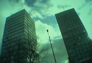 Kadr z filmu przedstawiający dwa wieżowce nachylone do środka kadru, pomiędzy nimi latarnia, w tle niebo z chmurami, całość w tonacji zielono-niebieskiej.