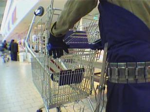 Kadr z filmu: widoczny fragment postaci w metalowym pasie, rękawicach i stroju roboczym, pchającej wózek sklepowy wzdłuż alejki w hipermarkecie.