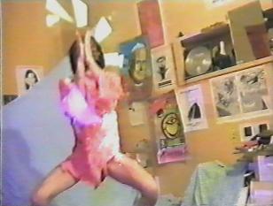 Zdjęcie rogu pokoju, którego pomarańczowe ściany pokryte są kolorowymi plakatami oraz rysunkami. Osoba w ciemnych włosach do ramion i w różowej koszulce trzyma złożone ręce przed twarzą. Stoi przodem, w rozkroku, jednak nogi ma zgięte.