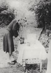 Czarno-biała fotografia przedstawiająca kobietę w ogrodzie, nachyloną nad stołem przykrytym białą serwetą i sadzącą geranium w doniczce, wysoka roślina zasłania jej twarz.