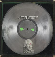 Zdjęcie płyty winylowej w kolorze srebrnym umieszczonej w gablocie, na górze napis Morris Generativ, na dole przyklejona wycięta z gazety głowa papieża, na środkowym okręgu dwa zielone serca odwrócone wierzchołkami do siebie.