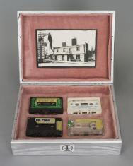 Zdjęcie pomalowanej na srebrno drewnianej skrzynki obitej w środku czerwonym materiałem, w jej dolnej części umieszczone płasko 4 kasety magnetofonowe opisane odręcznie na etykietach, na wnętrzu wieka czarno-białe zdjęcie przedstawiające budynek.