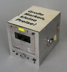 Zdjęcie prostopadłościennego magnetofonu z obudową w kolorze srebrnym, na wierzchu napis w języku niemieckim: Grosse Marken, kleine Preise!, nad okienkiem kasety napis Marcelo.
