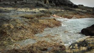 Kadr z filmu przedstawiający skalisty brzeg morski, w głębi po prawej stronie na brzegu leży odwrócony nagi mężczyzna w klasycznej pozie leżącej Wenus.