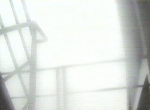 Kadr z filmu przedstawiający architektoniczną konstukcję we mgle.