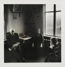 Czarno-biała fotografia portretowa. Przedstawia parę starszych osób we wnętrzu mieszkania. Mężczyzna i kobieta siedzą przy stole w rogu pomieszczenia. Na obu przyległych ścianach są okna, które oświetlają izbę. W rogu na pierwszym planie widać wrzeciono.
