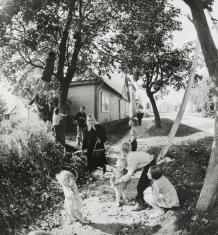 Czarno-biała fotografia. Scena rodzajowa na wiejskiej drodze, przed domem. W kadrze widać 10 osób. Głównie są to dzieci, które bawią się pod drzewami. Pozostałe postacie to starsza kobieta i mężczyzna, którzy idą wzdłuż drogi w stronę obiektywu.