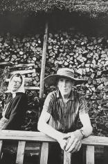 Czarno-biała fotografia portretowa. Przedstawia parę starszych osób na tle składowanego drewna na zewnątrz chaty. Mężczyzna patrzy w stronę obiektywu. Ma pogodną, twarz, nosi słomkowy kapelusz. Kobieta siedzi obok, uśmiecha się, na głowie ma chustę.