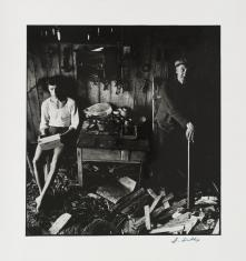 Czarno-biała fotografia. Portret dwóch mężczyzn w warsztacie stolarskim. Młody chłopak siedzi na krześle, ma zamyśloną twarz. Stary mężczyzna stoi o lasce, patrzy w stronę aparatu. Pomiędzy nimi jest stolik z narzędziami. Wokoło szczapy drewna.