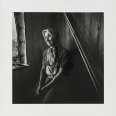 Czarno-biała fotografia. Portret starej kobiety w chuście. Postać siedzi w rogu pomieszczenia przy oknie. Jej sylwetka oświetlona jest światłem z zewnątrz. Oczy kobiety patrzą w stronę aparatu. Jej twarz jest uśmiechnięta.