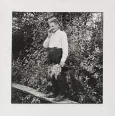 Czarno-biała fotografia. Portret starego mężczyzny z papierosem. Postać stoi na drewnianej kładce wśród bujnej roślinności. W ręku trzyma zerwane kwiaty. Widoczna jest  cała sylwetka mężczyzny.