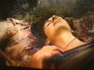 Kolorowy kadr. Portret kobiety, leżącej na plecach z zamkniętymi oczami. Kolorowe, rozmyte tło. Nad głową dziewczyny widoczna jest łuna białych promieni.