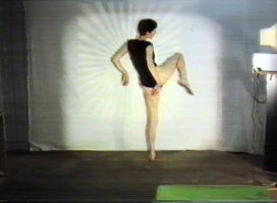 Kadr z filmu przedstawiający w centrum tańczącą młodą kobietę ubraną w czarne body, odwróconą tyłem, z prawą nogą uniesioną do góry, jej sylwetka jest oświetlona kwadratem światła, podłoga jest brązowa z zielonym elementem na brzegu kadru.