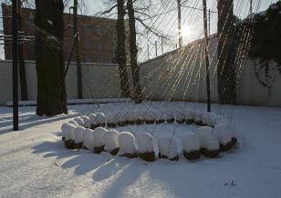 Zdjęcie przedstawiające dużych rozmiarów rzeźbę złożoną z ponad 30 polnych kamieni zawieszonych nad ziemią przy pomocy drutów i tworzących okręg,  w związku z tym że rzeźba jest w ogrodzie zimą, śnieg przykrywa kamienie, a słońce rozświetla strukturę.