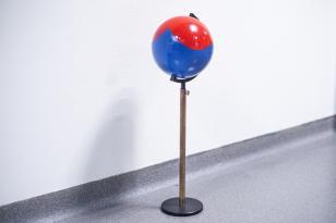 Na szarym tle ściany i podłogi widoczny globus osadzony na podstawce i metalowym pręcie, kula ma kolory czerwony i niebieski.