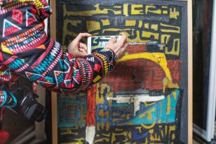 Zdjęcie abstrakcyjnego, kolorowego obrazu, fotografowanej telefonem komórkowym przez osobę w równie barwnej kurtce, po prawej stronie widoczne jest ramię tej osoby.