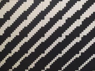 Na zdjęcu fragment pracy Ryszarda Winiarskiego - układ czarnych i białych kwadratów ułożonych pasowo naprzemiennie po przekątnej.