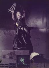 Kobieta w czarnej sukni w wyciągniętych w górę dłoniach trzyma dwie małe sztalugi, tło to ceglana ściana pomalowana na biało, na pierwszym planie telewizor z dołączonymi skrzydłami.