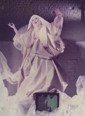 Kobieta w białej, obfitej, zakonnej szacie unosi ręce w górę w geście modlitwy, w fałdach szaty przed nią monitor telewizora, za nią ściana z cegły pomalowana na biało.