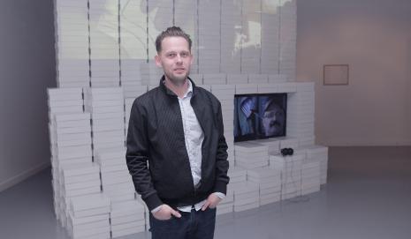 Piotr Wyrzykowski na tle swojej pracy Emotikon (współtwórca Robert Rumas)