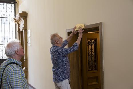 Członkowie grupy Łódź Kaliska Andrzej Makary Wielogórski i Marek Janiak przykręcają tabliczkę Czysta sztuka przy wejściu do toalety – muzeum Łodzi Kaliskiej