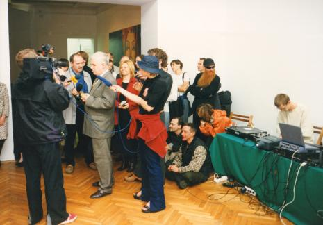 Jacek Ojrzyński (wicedyrektor ms) otwiera wystawę. Siedzą na podłodze Maciej Kostro (Dział Promocji) i Andrzej Miastkowski (Dział Realizacji Wystaw i Wydawnictw). Z brodą Mikołaj Robert Jurkowski (Centralny Urząd Kultury Technicznej), obok Wojciech Goczkowski (Dział Edukacji). Przy stole siedzi Maciej Sienkiewicz