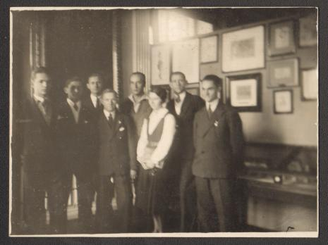 Na tle ekspozycji Władysław Strzemiński z uczniami III Kursu Publicznej Szkoły Dokształcającej Zawodowej nr 10 przy ul. Andrzeja 7 w Łodzi, po 1930