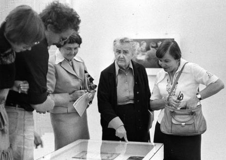 Żona artysty Aleksandra Szpakowska w otoczeniu widzów zwiedzających wystawę