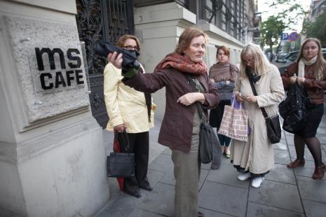 Krystyna Potocka (Galeria Manhattan w Łodzi) zaprasza widzów na wydarzenie, w jasnym płaszczu Ewa Partum