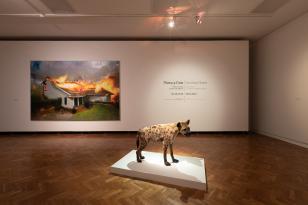 Zdjęcie sali wystawowej o białych ścianach i drewnianym parkiecie. Na środku znajduje się podest, na którym stoi wypchana hiena. Na ścianie po prawej widnieje nazwa, opis, a także data. Po lewej wisi obraz płonącego domu.